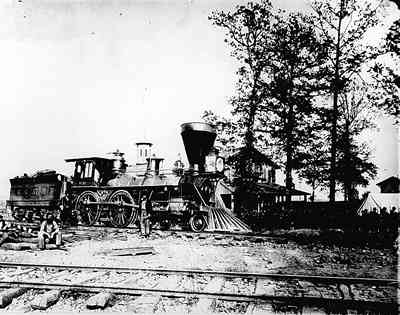 US military railroad engine no. 137,, built in 1864 in the yards of Chattanooga with troops lined up in background.